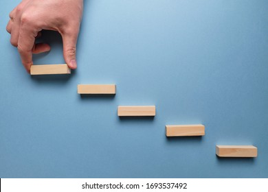 Concept of business development stages. Hand holds wooden blocks on a blue background. Close up.