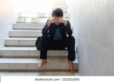 Concept of business failure : Young businessmen sit on the stairs and his hands clasped his head Because he is so desperate , stressed , sadness after knowing the bad news that he is unemployed.