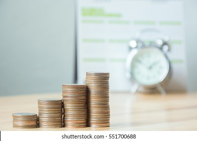 Concept business finance save money, Coins stack on wood table with blurred calendar and alarm clock