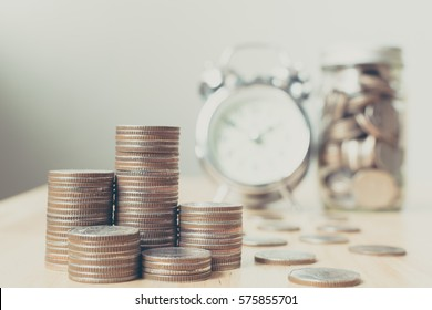 Concept business finance save money, Coins stack on wood table with blurred alarm clock and money in jar