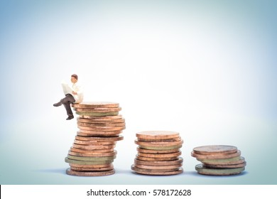 Concept of business investment learning. Businessman reading newspaper while sitting on coin stack.