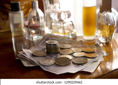 concept of business with money and perfumes on a wooden background