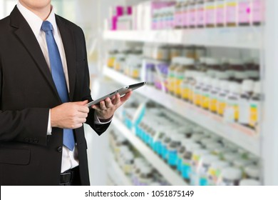 Concept of Business owner in pharmacy. Businessman using tablet to drug store stock management.