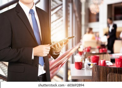 Concept of Business owner using tablet in restaurant with background of a hospitable waitress taking an order from customer