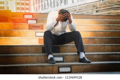 Concept business people failure and unemployment problem. Business men bankruptcy and debt sitting on the stairs with hands close his head. Unemployed businessman frustrated and desperate to find work