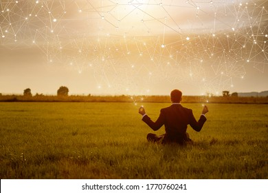 The concept of business recovery through innovative technologies. Young businessman is meditating against the backdrop of a sunny sunset on the Internet.