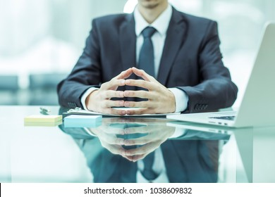 concept of business success:successful businessman sitting behind a Desk, hands folded in front of him.