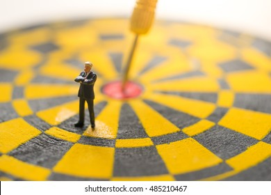 Concept of business target. Businessman with dart board with aroow on target.