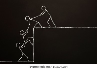 Concept of a business team helping each other to achieve success together drawn with chalk on blackboard with copy space.