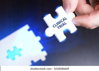 The concept of business, technology, the Internet and the network. A young businessman collects a puzzle with the proper inscription: Clinical trial