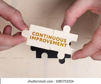 The concept of business, technology, the Internet and the network. A young businessman collects a puzzle with the proper inscription: Continuous improvement