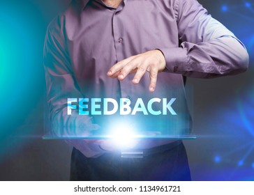 The concept of business, technology, the Internet and the network. A young entrepreneur working on a virtual screen of the future and sees the inscription: Feedback