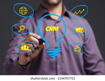 The concept of business, technology, the Internet and the network. Young businessman showing inscription: CRM