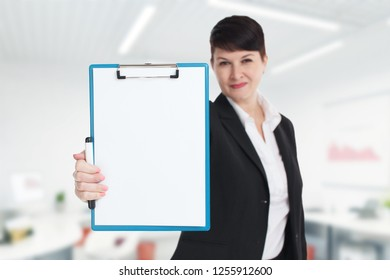 The concept of business, technology, the Internet and the network. Young entrepreneur showing blank clipboard. Success in business, job and education concept shot.