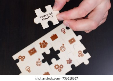 The concept of business, technology, the Internet and the network. A young businessman collects a puzzle with the proper inscription: Employee benefits