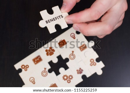 The concept of business, technology, the Internet and the network. A young businessman collects a puzzle with the proper inscription: Benefits