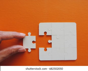 Concept of business,hand holding a puzzle piece on puzzle background.