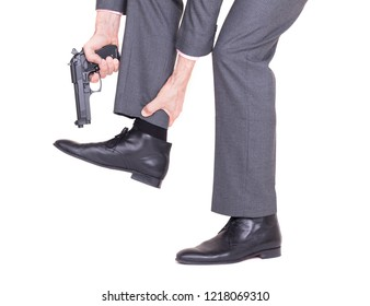 Concept - Businessman shooting himself in the foot with a handgun