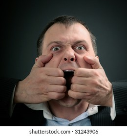 concept of a businessman tearing his angry scream apart, isolated on black
