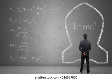 Concept of a businessman that solves problems of Albert Einsteins physical formula on concrete wall background