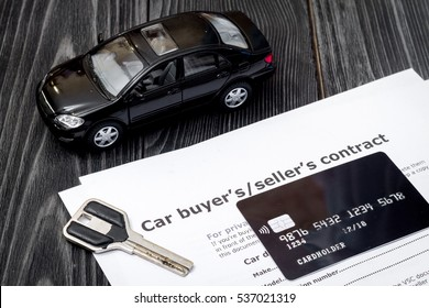 concept of buying car on dark wooden background