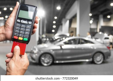 Concept of buying new car by paying by credit card at showroom. hands entering security pin in credit card reader.