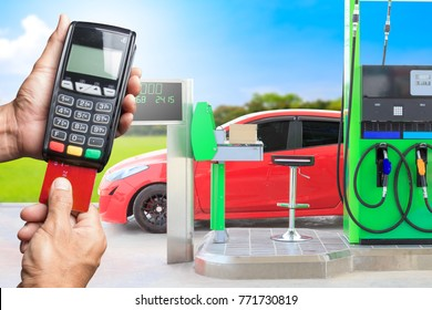 Concept of buying paying by credit card for gasoline at the station. hands entering security pin in credit card reader.
