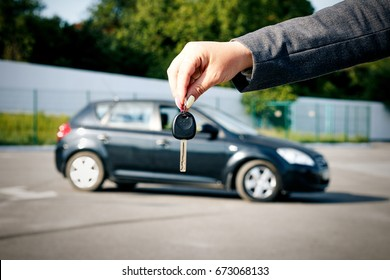 Concept of buying, selling and renting a car. A female hand holds the car key against the background of the car. With a place for advertising text.