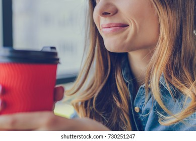 Concept of calmness and relaxation. Smiling woman holding a cup is going to drink coffee. She is sitting in a cafe near the window. Close up, cropped photo