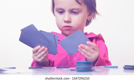 The concept of card games. Little cute child girl playing poker