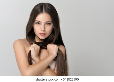 Concept of care long hair. Beautiful woman with bare shoulders has a clean well-groomed skin and long straight hair. Close-up portrait against a light gray background.