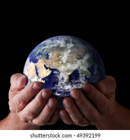Concept of caring for earth. Hands holding world with isolated black background. Earth image courtesy of NASA.