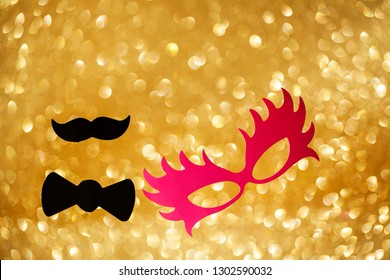 The concept of celebrating carnival on the background with the effect of radiant golden glitter. Holiday card. Carnival. Mardi gras. Masquerade. Empty place for festive text. The concept of the Purim.
