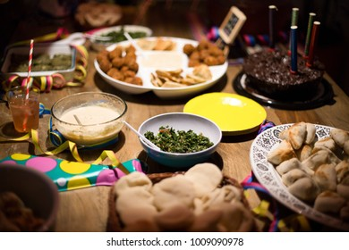 Concept celebration with family and friends. Birthday chocolate cake with arabic food: falafel, hummus, tahini, kibe, pitas and tabbouleh on rustic table. Food background. Middle East cuisine served.