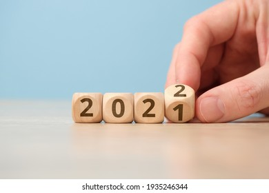 Concept of changing the year from 2021 to 2022 on wooden cubes by hand