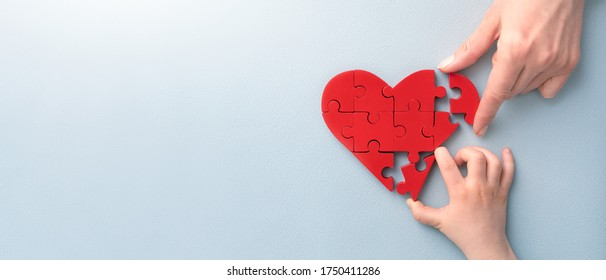 The concept of charity, love, donate and helping hand. International cardiology day. A woman and child arranges red heart shape puzzles. Symbol of helping others.