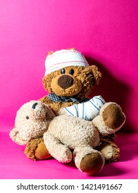 concept of child friendship and health assistance at the hospital with two injured teddy bears learning to treat each other, pink background
