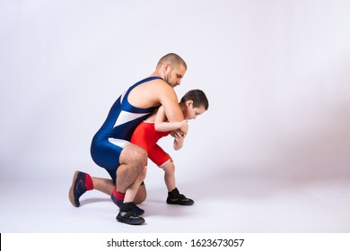 The concept of child power and martial arts training. Teaching children Greco-Roman wrestling. Boy and dad athletes in sportswear and wrestling equipment fight together on a white isolated background.