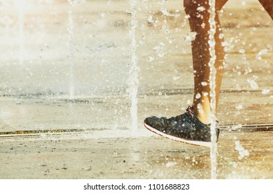Concept: child running through the fountain in a hot day