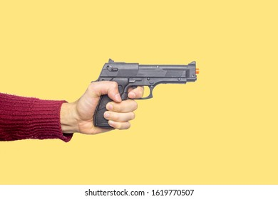 Concept of childhood, adults who don't want to grow up, play with kids, play like a child. Hand of a young man holding a yellow and green toy gun. Yellow background