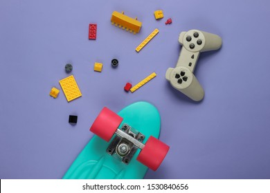 The concept of childhood, entertainment. Cruiser board, gamepad, toy bricks on purple background. Summer fun. Top view