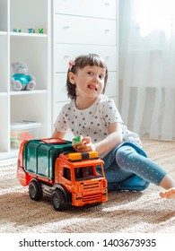 concept of childhood and people is a happy three year old curious girl playing with a toy car at home. Girl grimaces and shows tongue playing games for boys. The child is 3 years