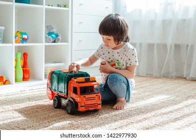 the concept of childhood and people is a happy three year old girl playing with a toy car at home. Girl playing games for boys. The child is 3 years