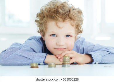 The concept of children's economic education. Boy build a tower using coins.