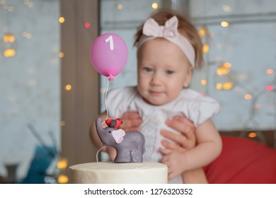 The concept of a children's holiday. Confectionery advertisment background. Mother hands holding one year old baby girl. First birthday celebration.