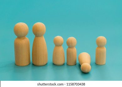 Concept of the child's death. Concept of the death of child, Loss. Wooden figurines of parents and children on a blue background. child's figure fell