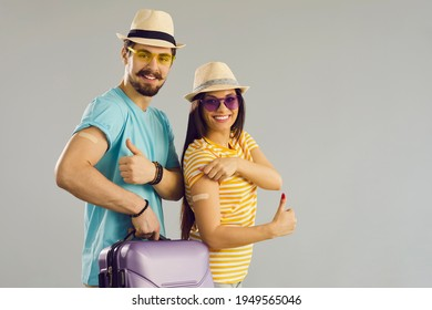 Concept of choosing vaccination for coronavirus infection. Happy smiling couple ready for safe travel giving thumbs-up OK okay sign gesture and showing arms with adhesive bandages after Covid-19 shot - Shutterstock ID 1949565046