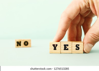 concept of choosing yes over no. man hand picking wooden cubes with text
