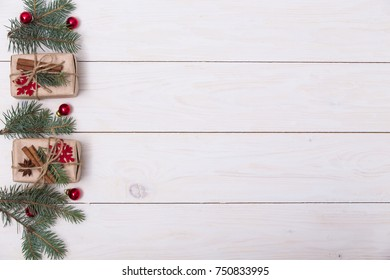 Concept christmas background with decorations, xmas tree and gift boxes on white wooden board. New year card. Empty space for your text.