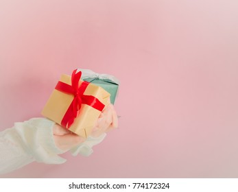 concept for christmas and new year event with beauty hand woman with winter cloth holding gift box and give it to pauper person with isolated pink background